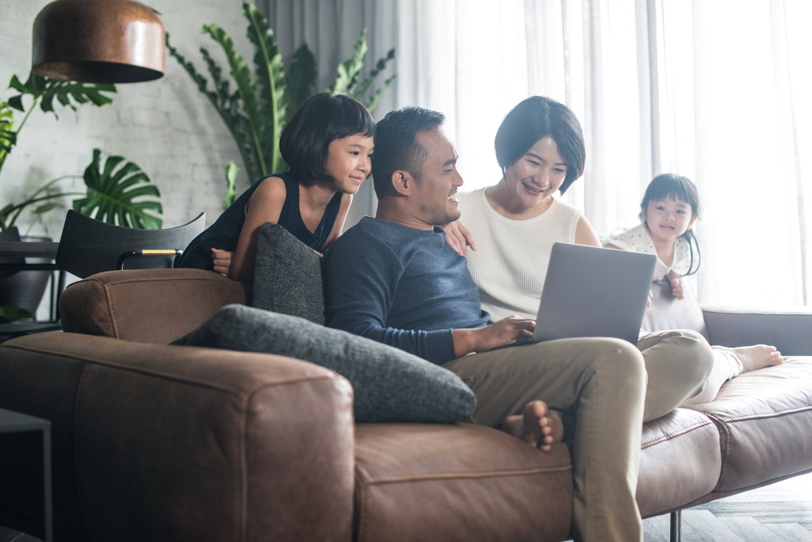 Young Asian family looking at laptop together